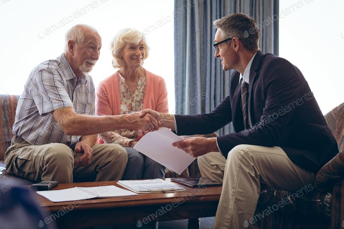Matured male physician interacting with senior  couple at retirement home. Both men shaking hands