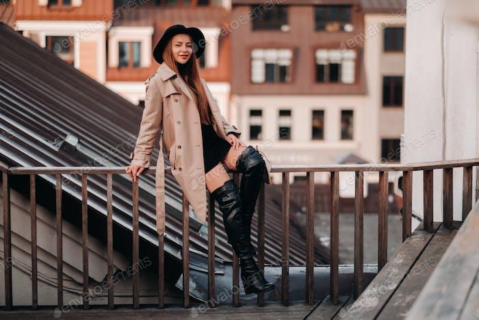 """Eine stilvolle junge Frau in einem beigen Mantel und schwarzem Hut sitzt auf einem Dach im Stadtzentrum. Frauen"""""""