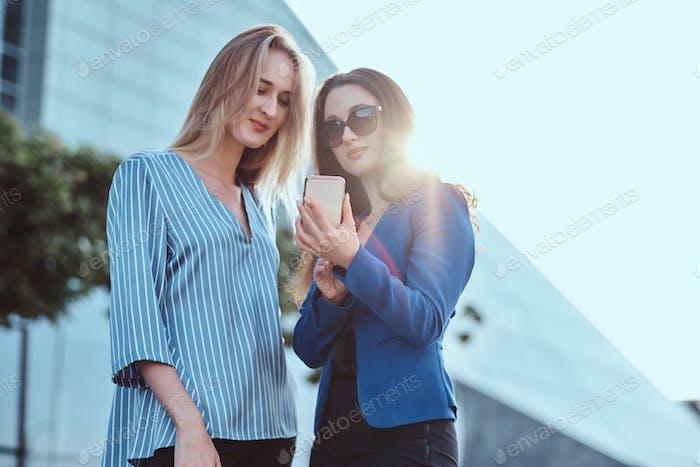 Zwei Frauen beobachten etwas auf dem Smartphone