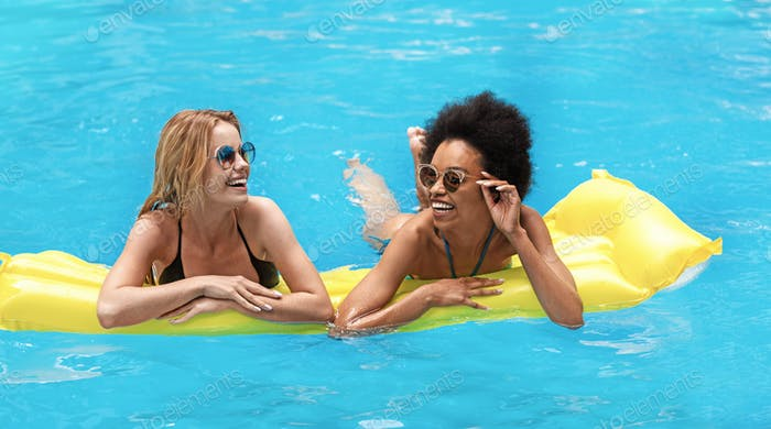 Summer fun together. Best girl friends floating on lilo and laughing at outdoor swimming pool