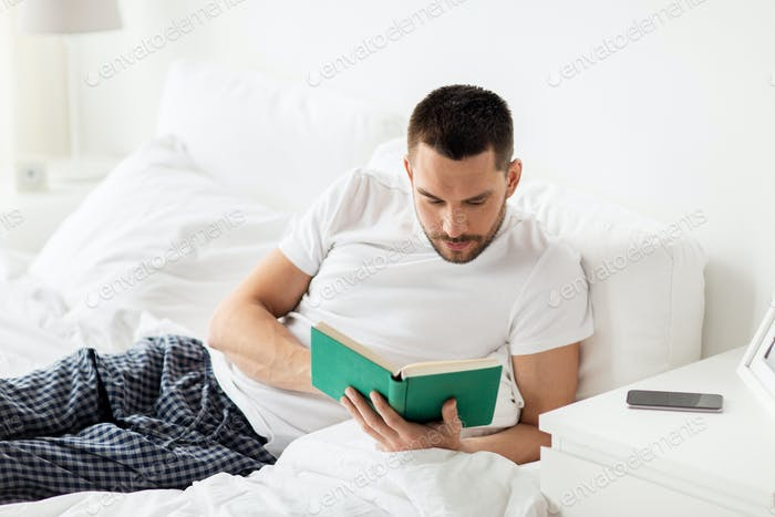 man reading book in bed at home