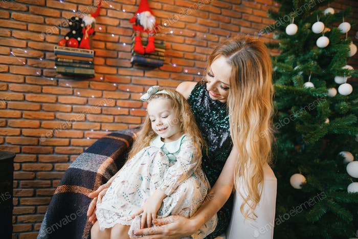 mother and daughter sitting by the christmas tree