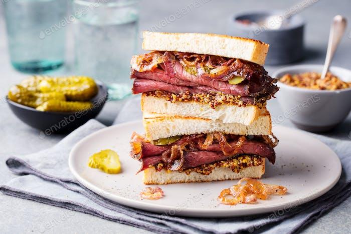 Roast Beef Sandwich auf einem Teller mit Gurken.