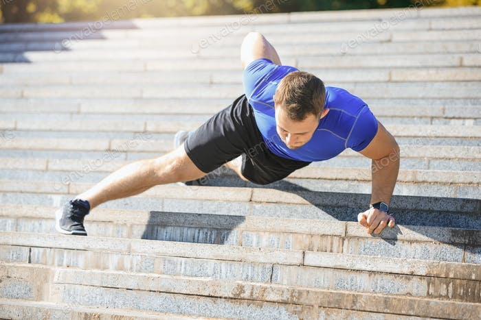 Fit man doing exercises outdoors at park