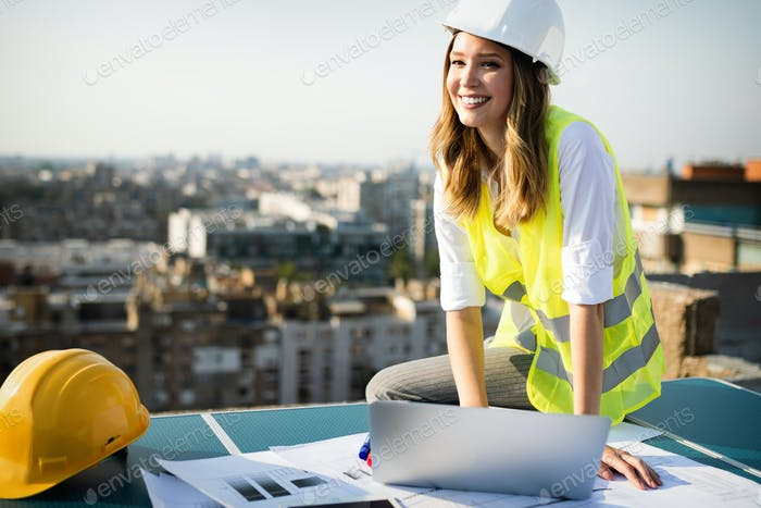 Portrait of engineer, architect young woman working on construction site