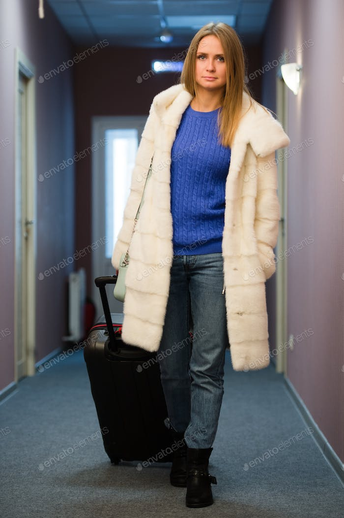 Pretty Young Blonde Woman Traveling Wearing a coat, jeans pulling a suit case