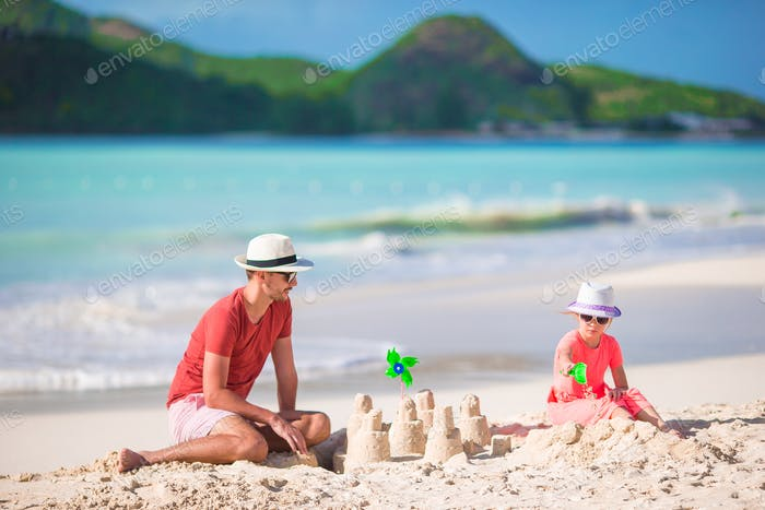 Father and little kid making sand castle at tropical beach