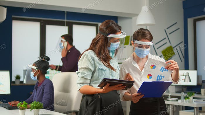 Coworkers with face visor in new normal office comparing graphs