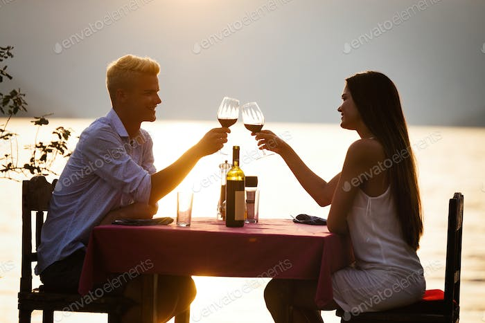 People, vacation, love and romance concept. Young couple enjoying a romantic dinner on beach