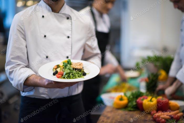 Chef Hände halten Gericht gebratenen Lachs Fischfilet