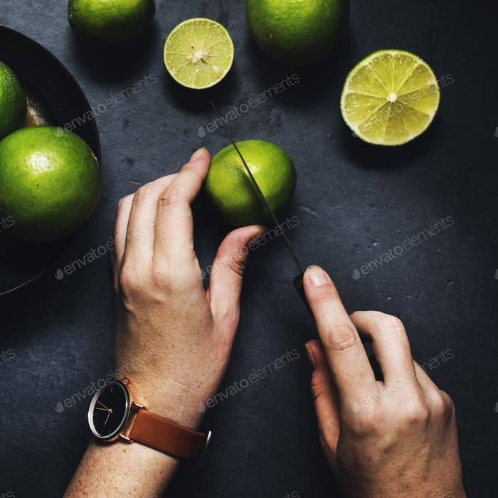 Aerial view of hands with knife cutting lime
