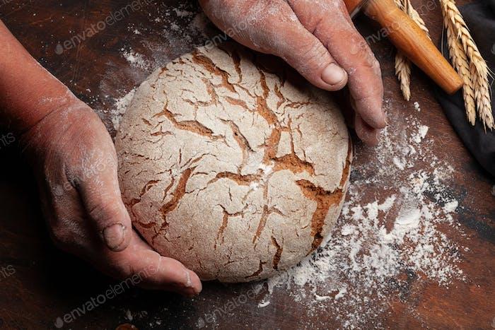 Baker holding fresh baked homemade bread