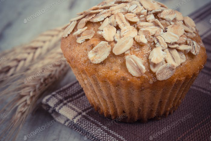 Vintage photo, Fresh muffin with oatmeal and ears of rye grain on checkered tablecloth