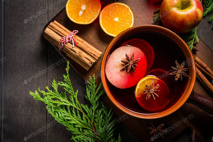 Spicy mulled wine with orange, apple, cinnamon and anise in pot