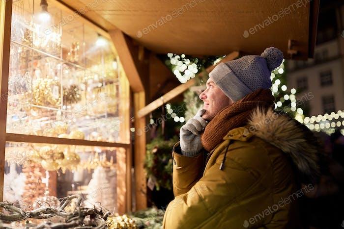 happy man looking at christmas market shop window