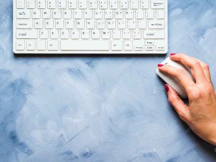 Blauer Hintergrund mit Frauenhand und Tastatur