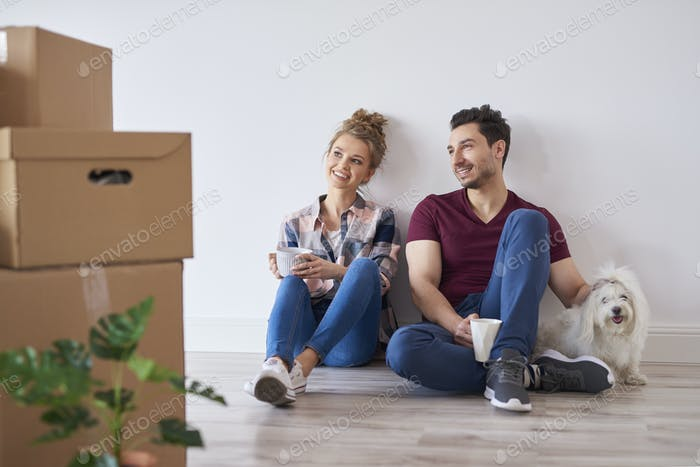 Smiling couple with coffee cups relaxing in their new home