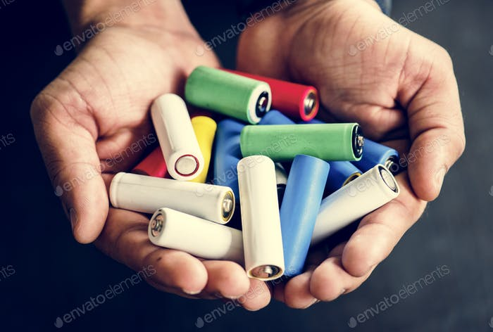 Hands holding various alkaline battery