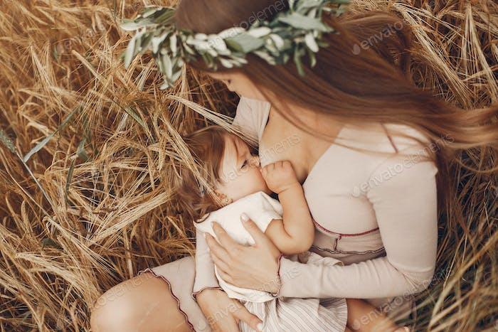 Elegante Mutter mit niedlichen kleinen Tochter in einem Feld