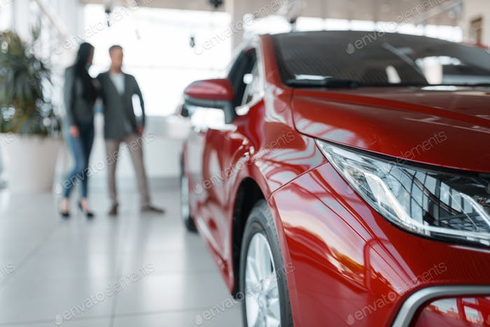 Couple buying new red car in showroom