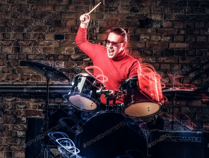 Stylish musician in sunglasses emotionally playing drums against brick wall background