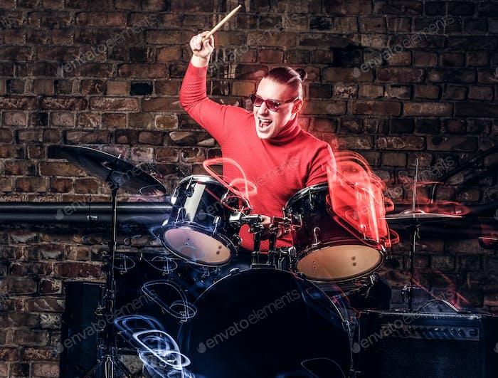 Stilvolle Musiker in Sonnenbrille emotional spielen Schlagzeug vor Backsteinwand Hintergrund