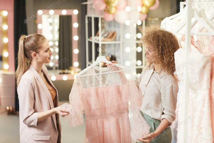 Shop Assistant Helping Client in Boutique