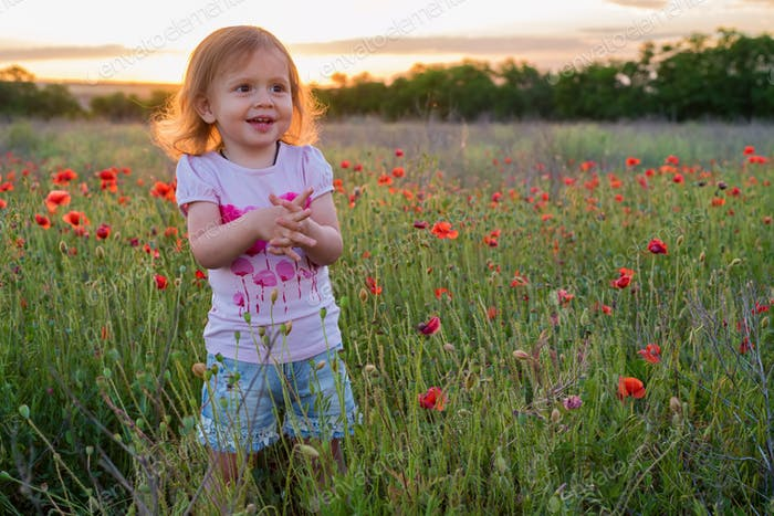 Cute happy child girl in poppy field. Happy childhood concept
