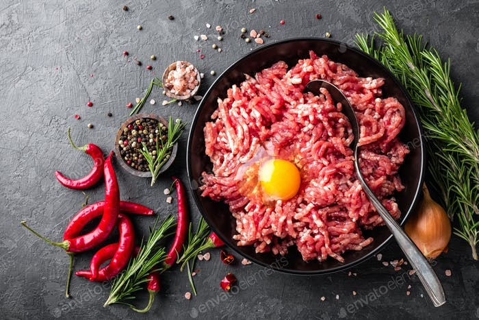 Hackfleisch. Hackfleisch mit Zutaten zum Kochen auf schwarzem Hintergrund. Ansicht von oben