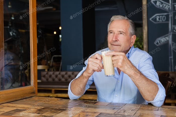 Senior thoughtful man holding cold coffee