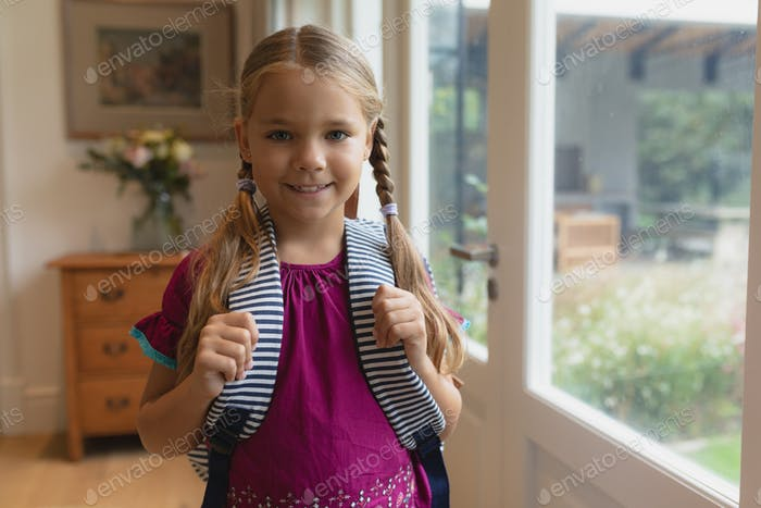 Front view of happy cute Caucasian girl with school bag looking at camera in a comfortable home
