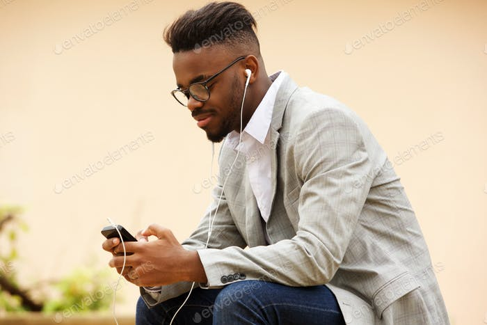 young guy sitting outside listening to music with mobile phone