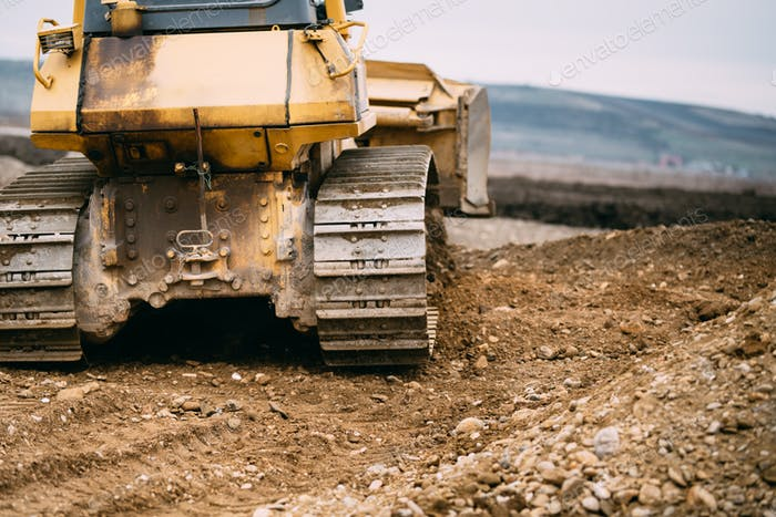 Close up details of bulldozer pushing earth and leveling ground on construction site