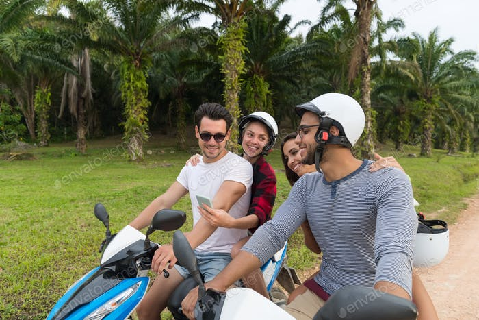 Two Couple Riding Motorbike, Young Man And Woman Travel On Bike On Tropical Forest Road