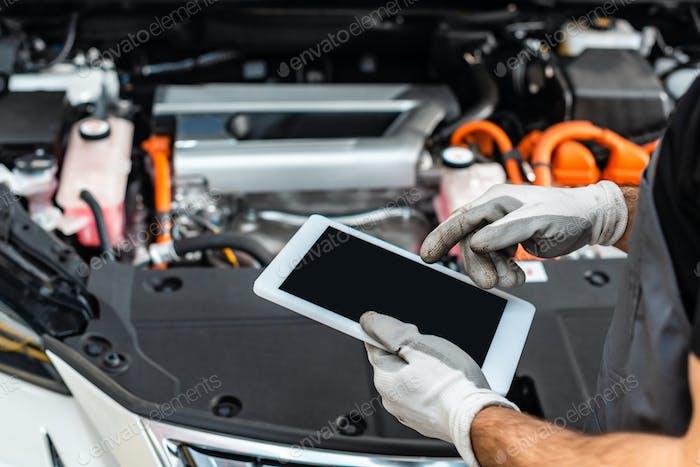 vista recortada del mecánico usando tableta digital cerca del compartimento del motor del automóvil