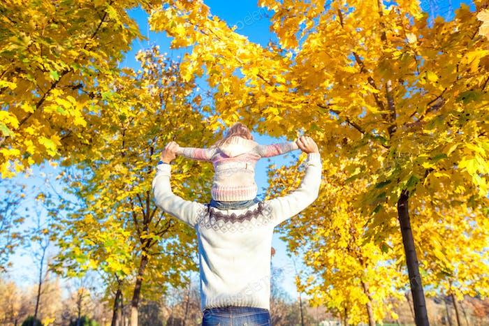 Kleines Mädchen Reiten auf den Schultern des Vaters im Herbst Park