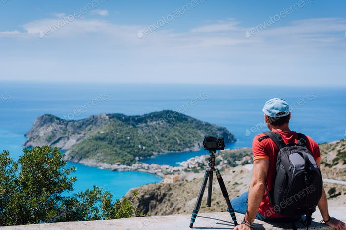 Summer holiday weekend visiting Greece Europe. Male freelance photographer with backpack enjoying