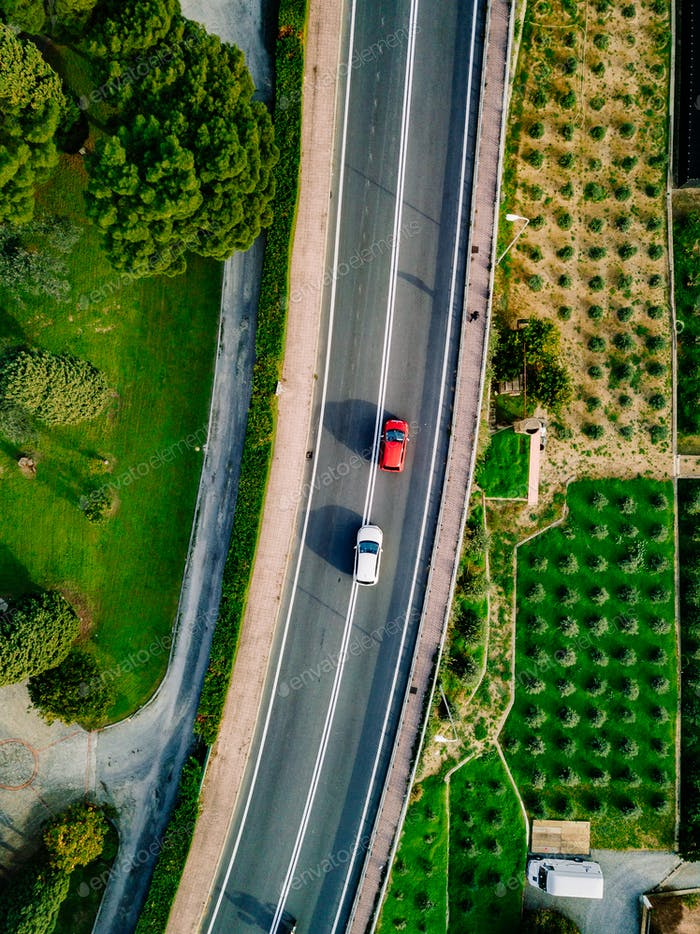 Aerial view of the asphalt road with cars going among the agricultural fields in Italy