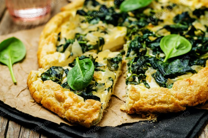 Spinach Ricotta Galette with fresh spinach leaves on a wood background