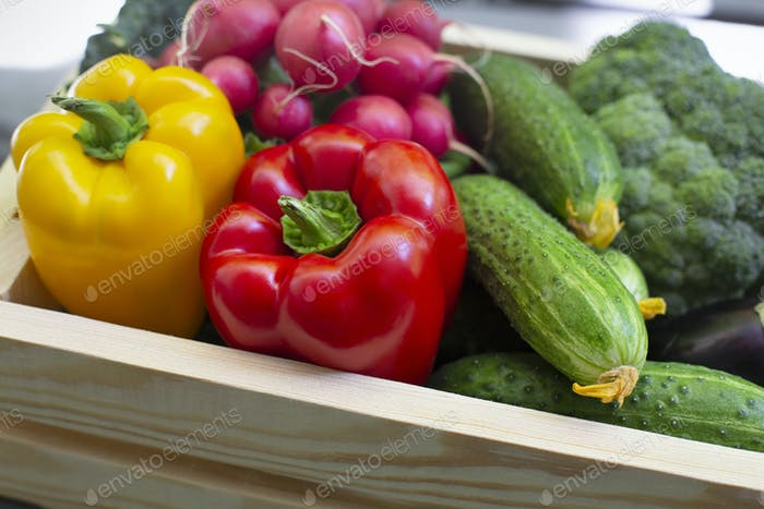 Close up of fresh organic vegetables in wooden box