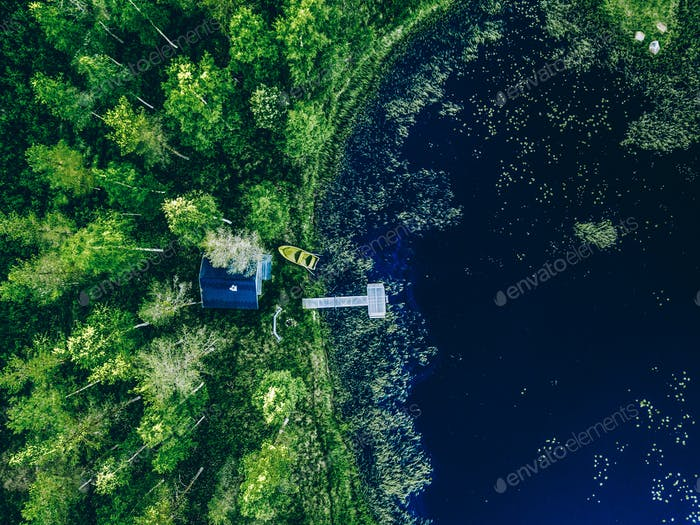 Aerial view of Sauna house by the lake shore.  Wooden pier with fishing boat.