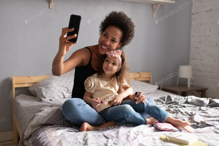 Cheerful ethnic mother with daughter making video call on smartphone