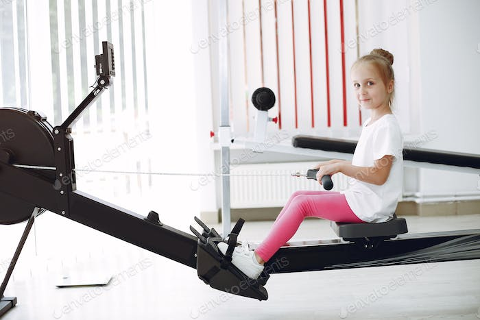 Cute little girl are engaged in gymnastics in the gym