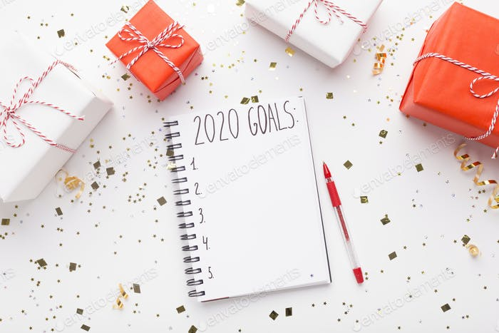 Notepad with goals and Christmas presents on white