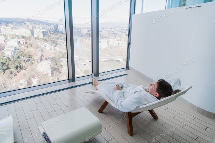 Young man resting on modern deck chair in front of big window with city view in modern spa