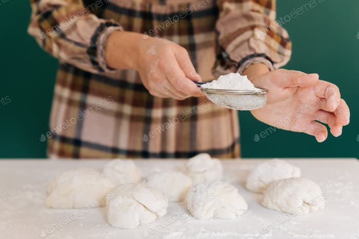 Woman sprinkles flour to handmade pieces of dough for bread, homemade cooking.