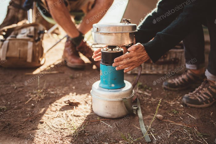 Woman camper warming her hands on camp stove
