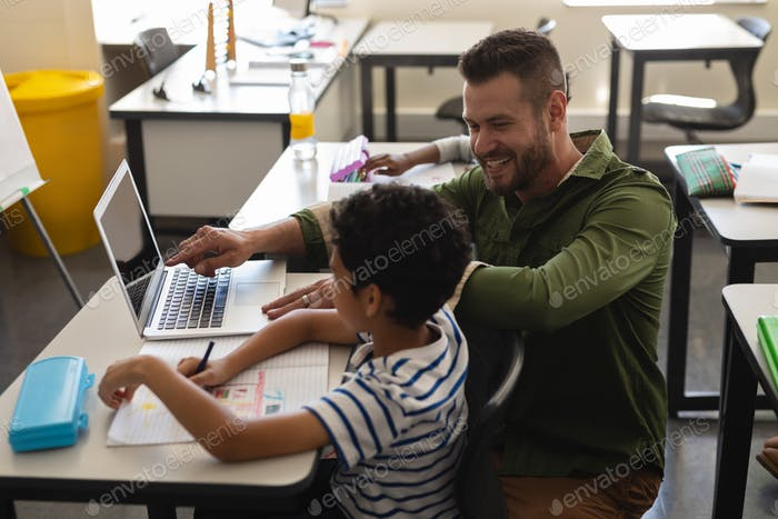 Side view of young school teacher helping boy with study on laptop in classroom
