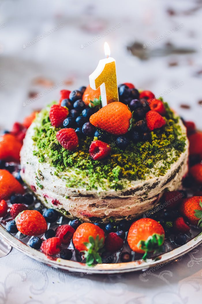 Birthday cake with one year figure and fresh fruits