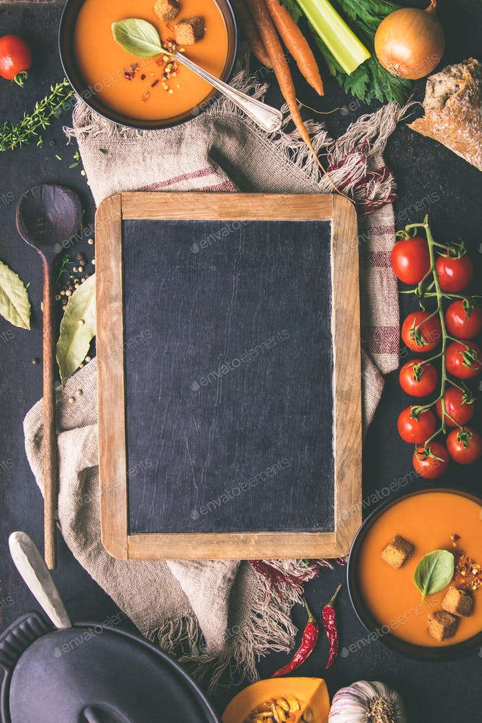 Tomato soup and fresh ingredients around vintage chalkboard